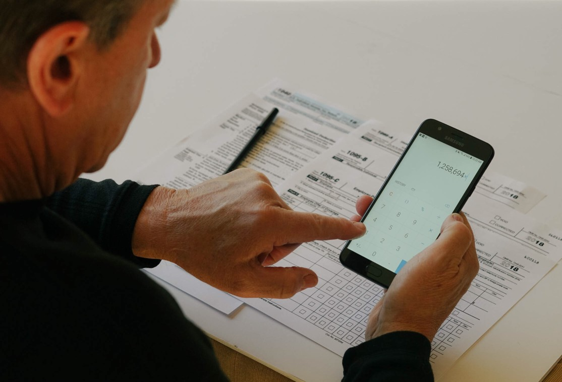 over-the-shoulder-view-of-a-man-using-a-mobile-calculator-and-filling-out-tax-forms_t20_VL9xO6